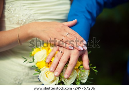 two hands with wedding rings on a background of yellow bridal bouquet - stock photo