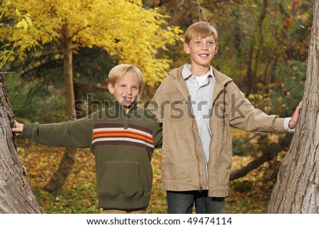 two handsome blond boys standing between trees in fall - stock photo