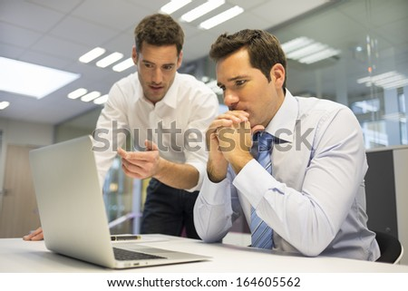 Two handsome businessmen working together on a project in the office - stock photo