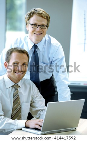 Two handsome businessmen working together on a project on laptop computer - stock photo
