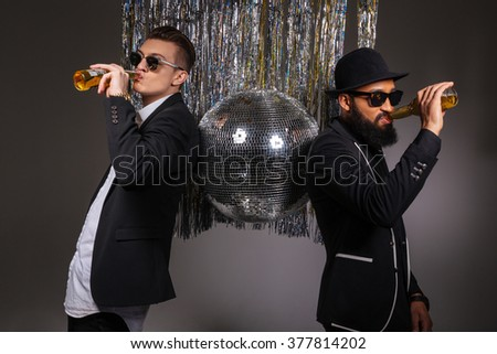 Two handsome confident young men in black suits and sunglasses standing near disco ball and drinking beer over black background - stock photo