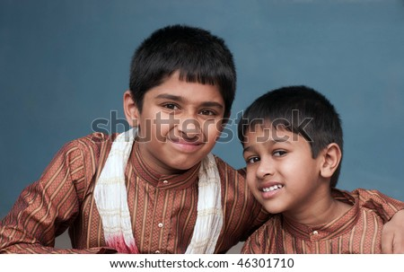 two handsome indian brothers looking happy - stock photo