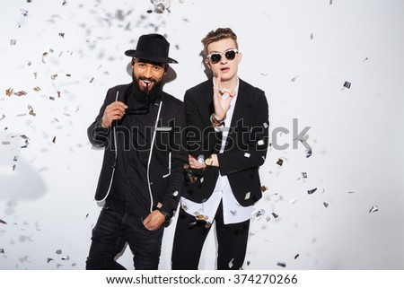 Two handsome men in fashion cloth standing isolated on a white background - stock photo