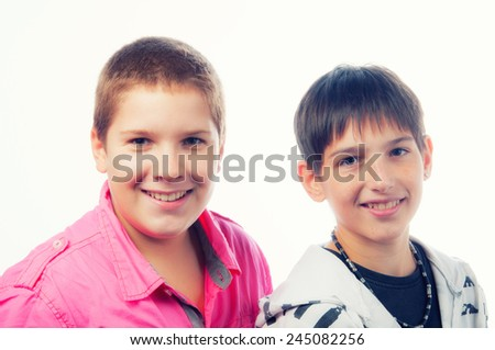 Two handsome teenage boys smiling isolated on white background.