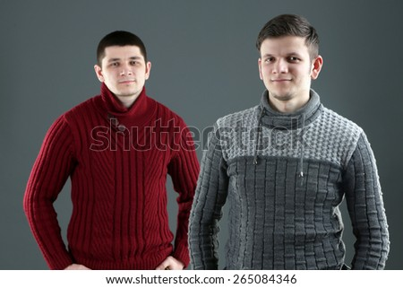 Two handsome young men on gray background - stock photo