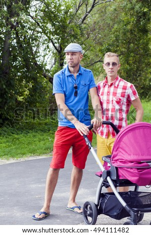 Two handsome young men with a baby stroller