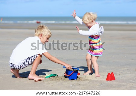 Two happy active children, teenage boy with his little sister, cute blonde toddler girl, playing with plastic toys building sand castles sitting on wide sandy beach at the sea - stock photo