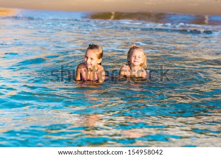 Two happy adorable kids playing in the sea on a beach - stock photo