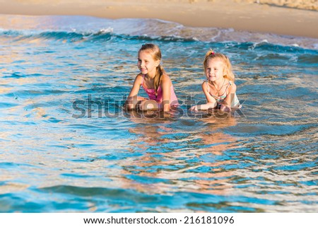 Two happy adorable kids playing in the sea on a beach