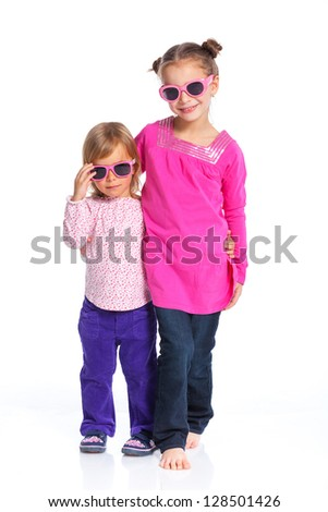 Two happy adorable smiling sisters in sunglasses. Isolated white background - stock photo