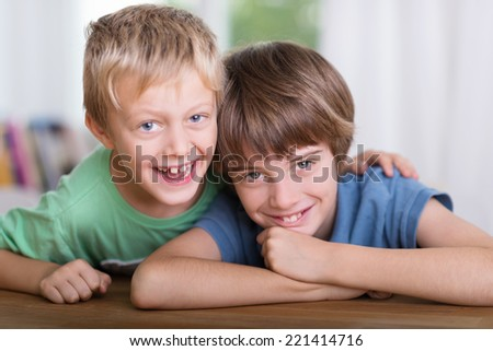 Two happy affectionate young brothers leaning on a table arm in arm grinning playfully at the camera - stock photo