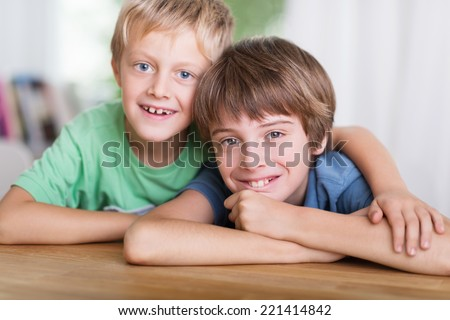 Two happy affectionate young brothers posing leaning on a wooden table with their arms around each other looking at the camera