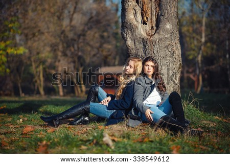 Two happy and cheerful young girl student, blond and brunette in coat and jeans laughing in sunny autumn park full of fallen leaves, horizontal pictures