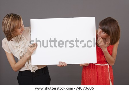 two happy and surprised women holding a white banner over grey background - stock photo