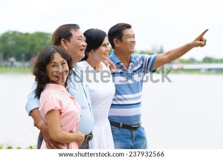 Two happy Asian senior couples outdoors - stock photo