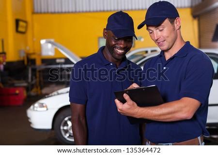two happy auto mechanics going through checklist inside workshop - stock photo