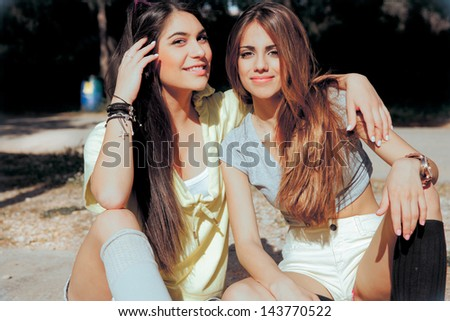 two happy, beautiful best friends sitting in park on a summer day and smiling. horizontal shot. soft sunny colors - stock photo