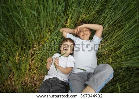 two happy boy lay in grass outdoors - stock photo