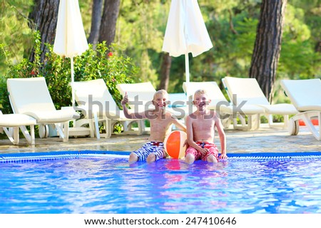 Two happy boys, laughing teenage twin brother, enjoying sunny summer vacation playing with inflatable ball in outdoors swimming pool - stock photo