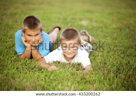 Two happy boys lying down on the grass
