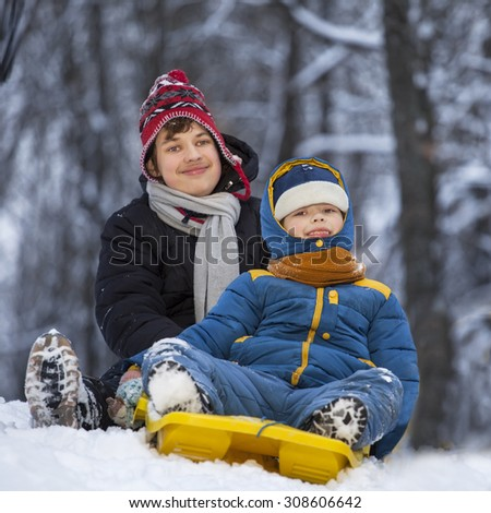 two happy boys on sled play - stock photo