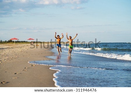 Two happy boys running on the sea beach at summer with raised arms