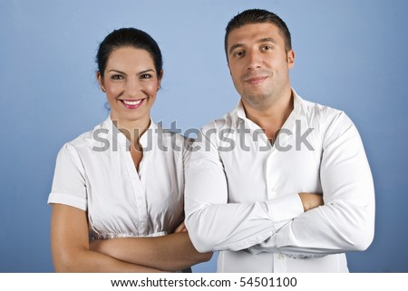 Two happy business man and woman standing with arms crossed and smiling dressed in white shirts on blue background - stock photo