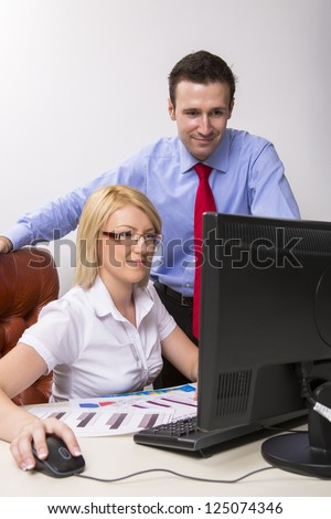 Two happy business partners working on computer in their office. - stock photo