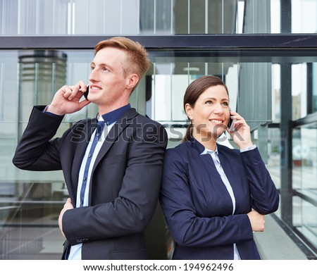 Two happy business people in front of office making calls with their smartphone - stock photo
