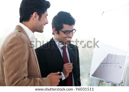 two happy businessmen discussing business strategy in a meeting, Indian business man with latin american colleague - stock photo