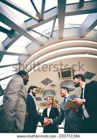 Two happy businessmen handshaking with their colleagues near by - stock photo