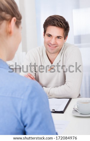 Two Happy Businesspeople Talking With Each Other At Workplace - stock photo