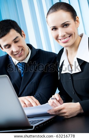 Two happy businesspeople working together at office - stock photo