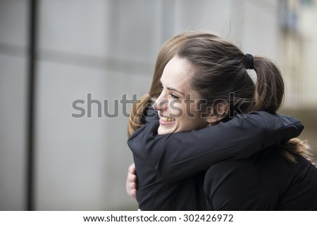 Two happy Businesswomen hugging each other outside office building. - stock photo