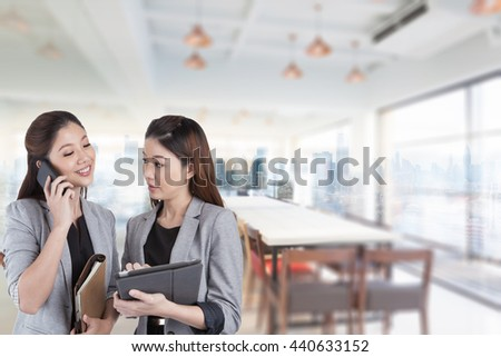 Two happy businesswomen standing and talking mobile phone with tablet on meeting room background.