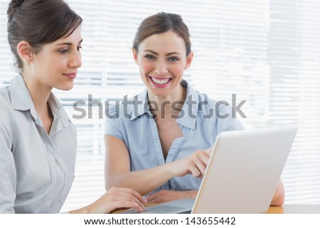 Two happy businesswomen working on laptop together at desk in office - stock photo
