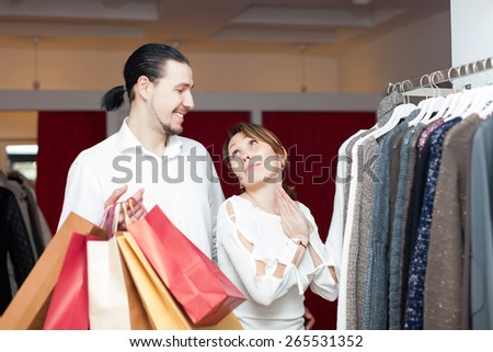 Two happy buyers with shopping bags  at clothing shop
