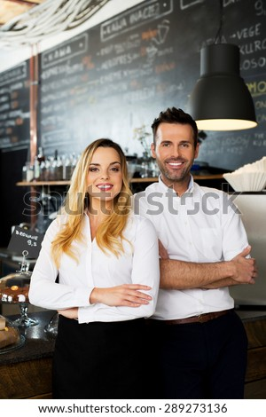 Two happy cafe managers standing at front of the bar - stock photo