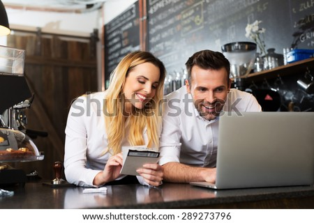 Two happy cafe managers working on laptop - stock photo