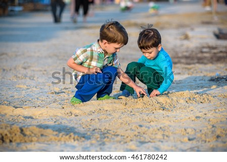 Two happy caucasian kids, brothers, playing together with toy cars sitting outdoors at pebble beach against the sea beach