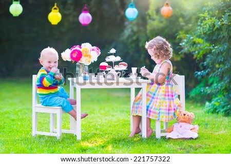 Two happy children, cute curly toddler girl and a little baby boy, brother and sister, enjoying a tea party with their toys playing with dishes, cup cakes and muffins in a sunny summer garden - stock photo