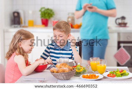 Two happy children eating breakfast during father works in background
