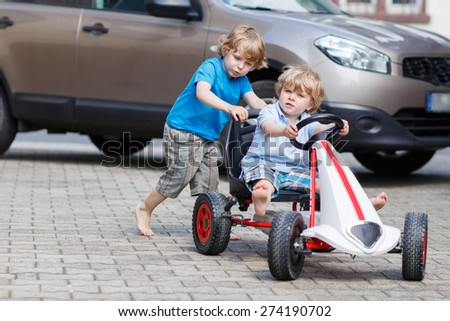 Two happy children having fun with toy race car in summer garden, outdoors. Active brother pushing the car with younger boy. Outdoor games for children in summer concept. - stock photo