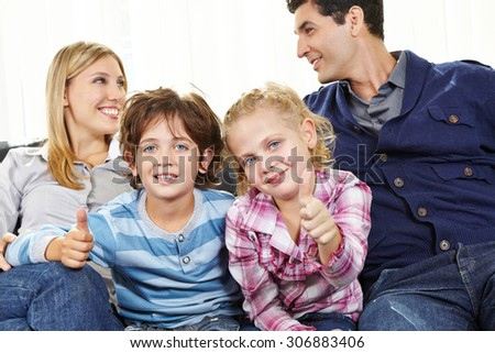 Two happy children holding thumbs up between parents on a sofa