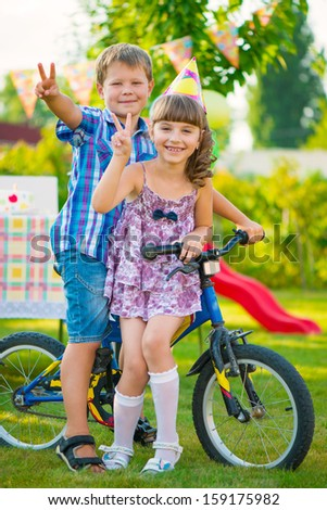 Two happy children in love sitting on bicycle - stock photo