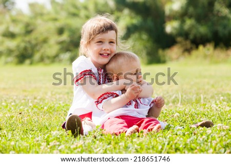 Two happy children in russian folk clothes on grass meadow