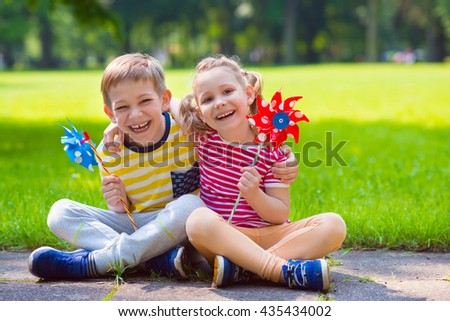 Two happy children playing in garden with windmill - stock photo