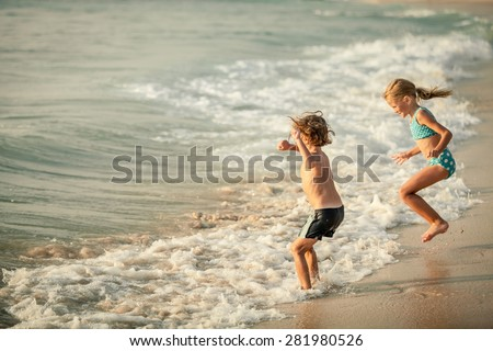 Two happy children  playing on the beach at the day time - stock photo