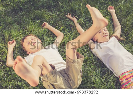 Two happy children playing on the grass at the day time. Concept Brother And Sister Together Forever
