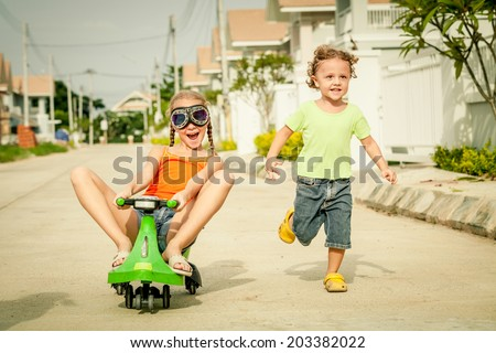 two happy children playing on the road at the day time - stock photo